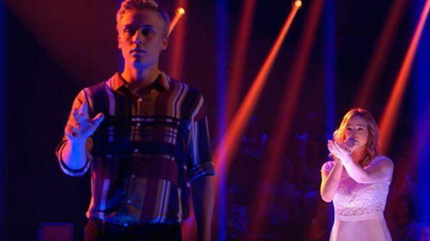 David steht im Vordergrund, Veronika dahinter, singt und streckt die Hand aus