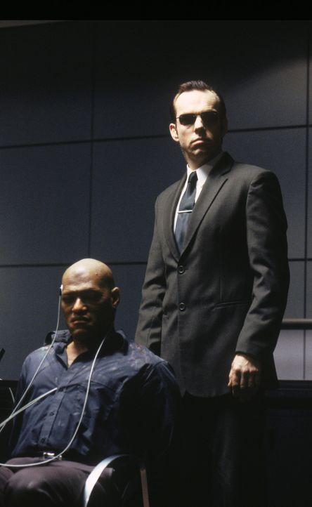 Agent Smith (Hugo Weaving, r.) foltert Morpheus (Laurence Fishburne, l.), um herauszukriegen, wo die geheime Stadt der Menschen ist. - Bildquelle: Warner Bros. Pictures