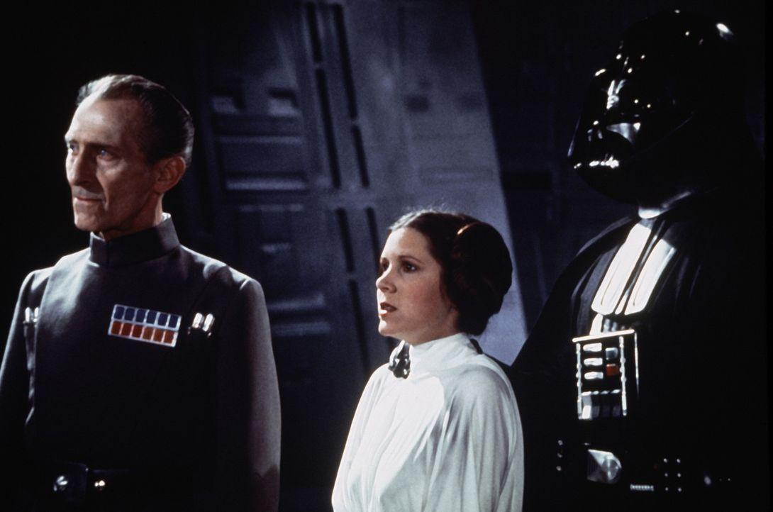 Unglücklicherweise gibt Prinzessin Leia (Carrie Fisher, M.) den Erpressern Vader (David Prowse, r.) und Admiral Tarkin (Peter Cushing, l.) nach. Di... - Bildquelle: Lucasfilm LTD. & TM. All Rights Reserved.