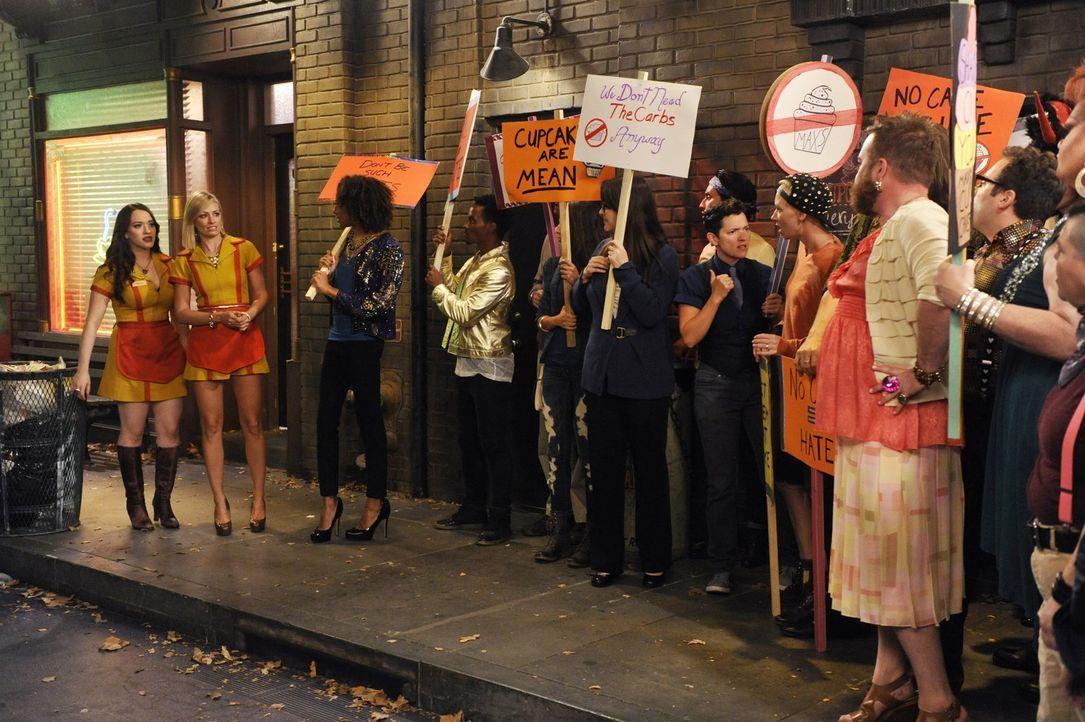 Sind Caroline (Beth Behrs, 2.v.l.) und Max (Kat Dennings, l.) wirklich schwulenfeindlich? Das behaupten zumindest die Demonstranten, die sich vor de... - Bildquelle: Warner Brothers