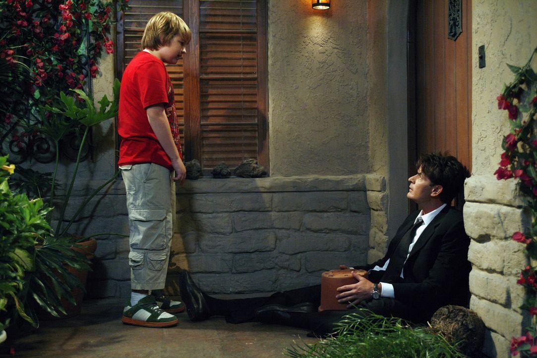 Jake (Angus T. Jones, l.) trifft auf seinen Onkel Charlie (Charlie Sheen, r.) vor der Haustür und bemerkt, dass irgendetwas mit ihm nicht stimmt ... - Bildquelle: Warner Brothers Entertainment Inc.