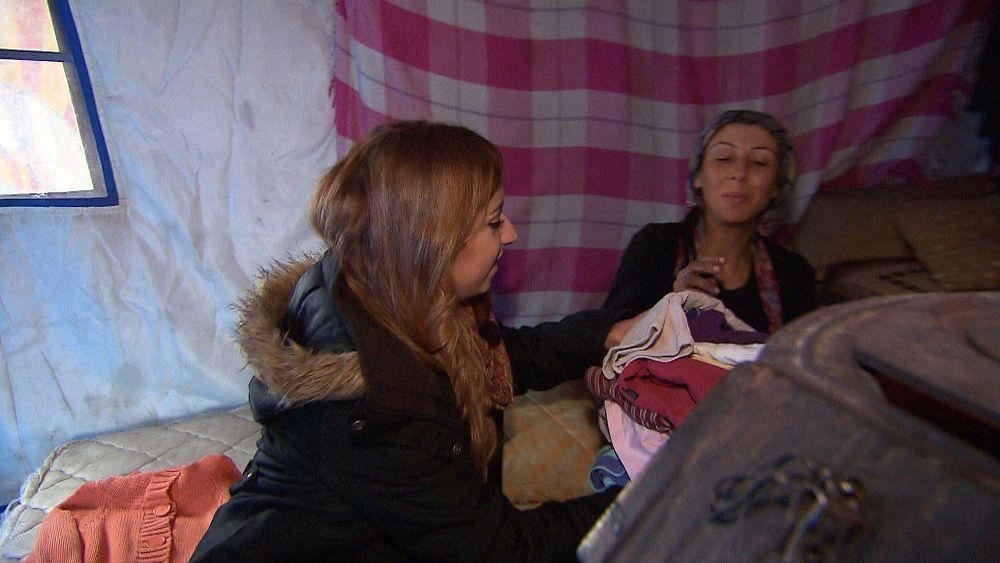 Sherin gibt einer schwangeren Frau Babykleidung