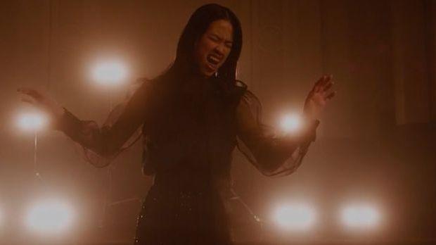 Claudia steht im langen Kleid in einem Saal und singt leidenschaftlich
