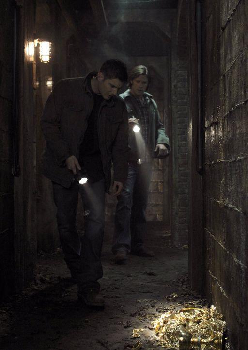 Als Sam (Jared Padalecki, r.) und Dean (Jensen Ackles, l.) auf eine Ansammlung von Goldstücken treffen, ist ihnen klar, dass der Feind nicht mehr w... - Bildquelle: Warner Bros. Television
