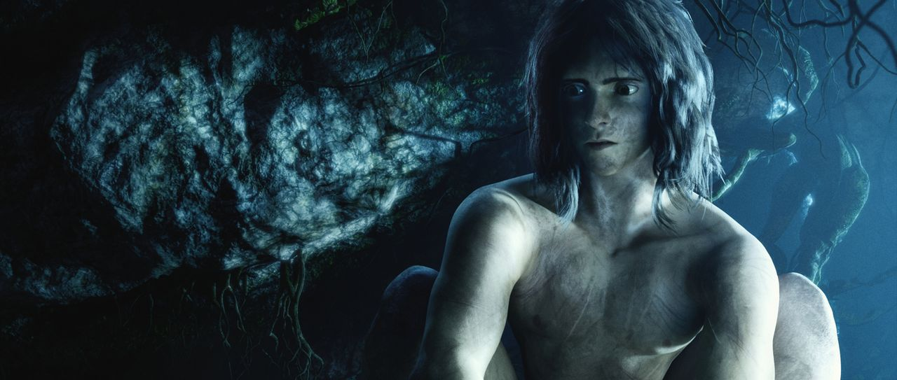 Vom Dschungel gezeichnet sitzt Tarzan nachdenklich in einer dunklen Höhle des Dschungels. - Bildquelle: Constantin Film