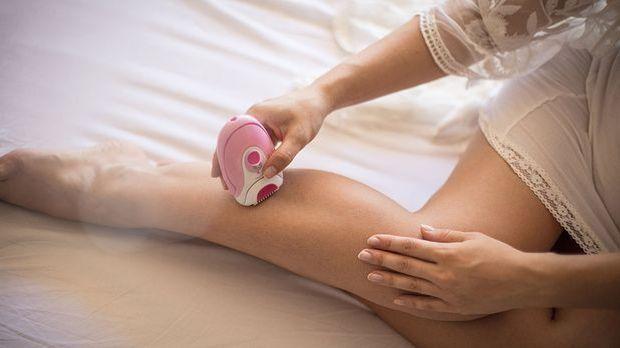 Frau epiliert ihre Beine