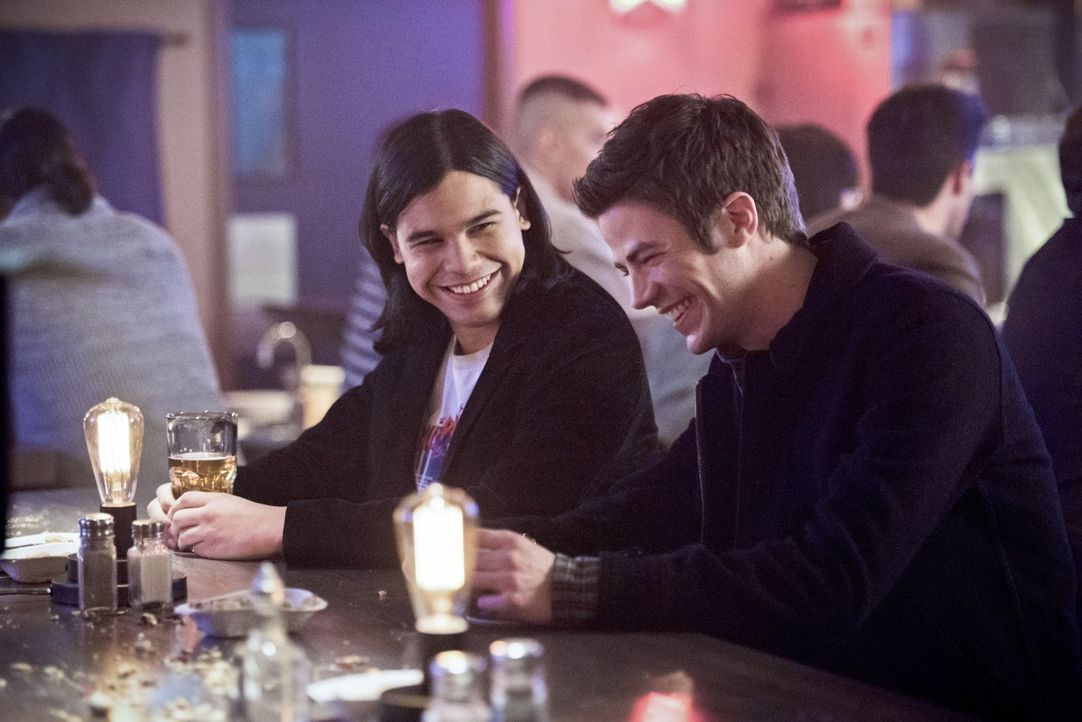 Als Cisco (Carlos Valdes, l.) und Barry (Grant Gustin, r.) in einer Bar angesprochen werden, ahnen sie nicht, wer die hübsche Frau wirklich ist ... - Bildquelle: Warner Brothers.