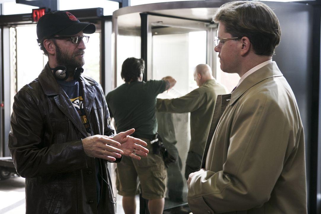 Regisseur Steven Soderbergh (l.) erteilt Regieanweisungen an seinen Hauptdarsteller Matt Damon (r.) - Bildquelle: Warner Bros. Pictures
