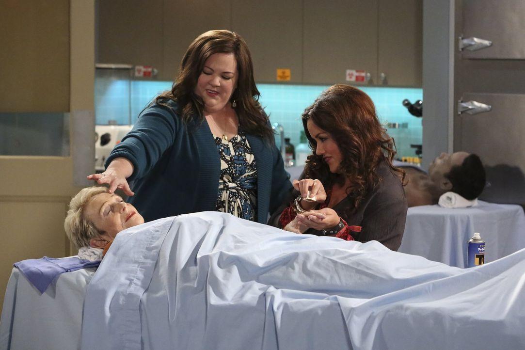 Molly (Melissa McCarthy, M.) begleitet Victoria (Katy Mixon, r.) zu ihrem Arbeitsplatz im Bestattungsunternehmen, um weiter für ihren Roman zu reche... - Bildquelle: Warner Brothers