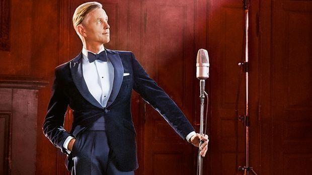 Max Raabe steht im Anzug lässig da, mit einem altmodischen Mikrofon in der li...