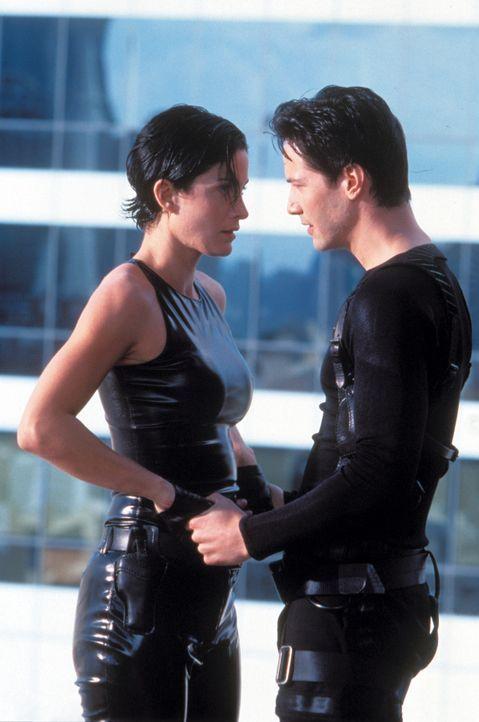 Neo (Keanu Reeves, r.) entdeckt etwas ganz Reales in der künstlichen Welt der Matrix: seine Liebe zu Trinity (Carrie Anne Moss, l.). - Bildquelle: Warner Bros. Pictures