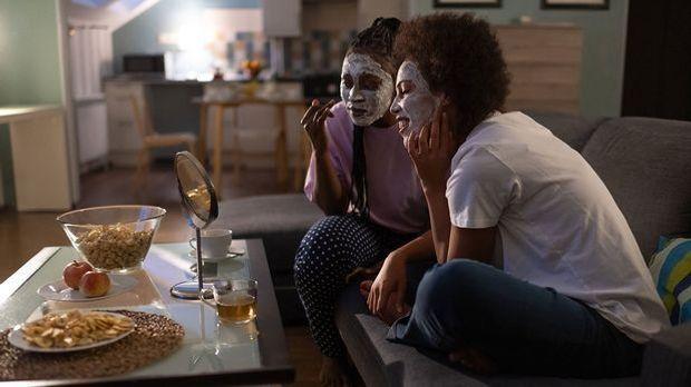 Gesichtsmasken machen zusammen mit Freunden