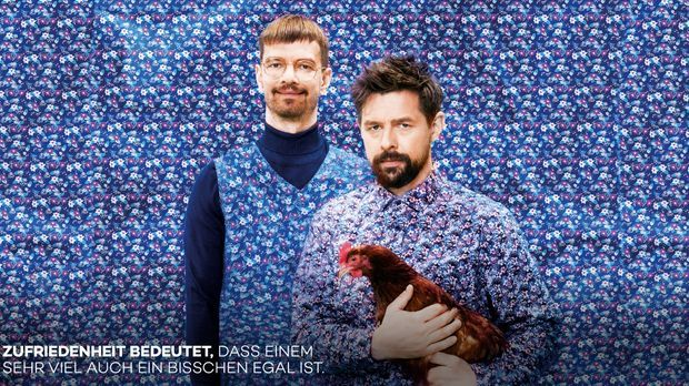Joko und Klaas tragen Pullover und Pollunder im gleichen Muster wie die Tapet...