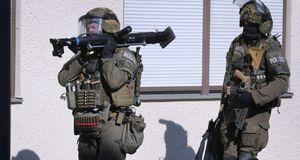 Spezialeinsatzkräfte der Polizei verlassen ein Studentenwohnheim im Augsburge...