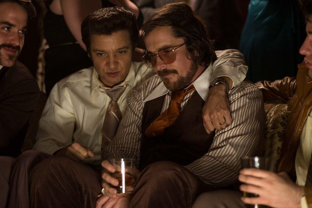 Um seinen eigenen Kopf zu retten, soll Irving Rosenfeld (Christian Bale, r.) seinen neuen Freund, Bürgermeister Carmine Polito (Jeremy Renner, M.),... - Bildquelle: TOBIS TFILM