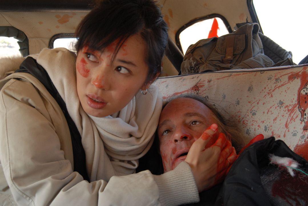 Verzweifelt versucht Anika (Nan Yu, l.), Chambers (William Shriver, r.) dem Tod noch zu entreißen. Doch ihr Stiefvater erliegt seinen schweren Verle...
