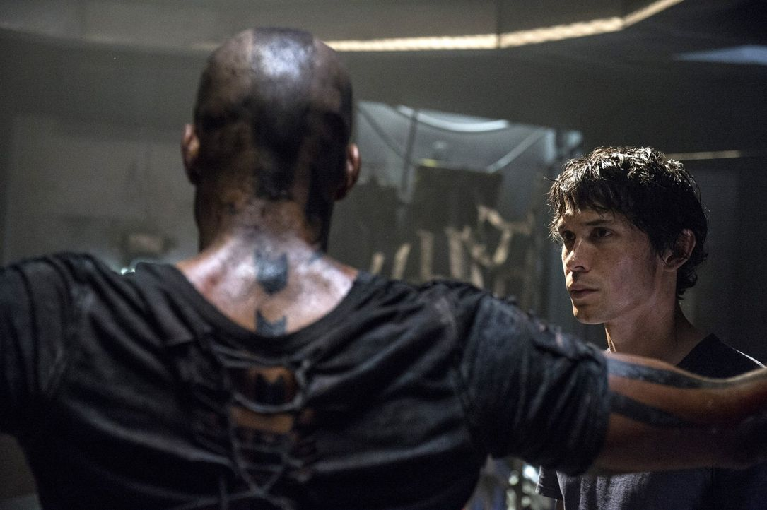 Während Bellamy (Bob Morley, r.) auf der Erde nach Antworten bei seinem Gefangenen (Ricky Whittle, l.) sucht, fordern auch die Menschen auf dem Raum... - Bildquelle: Warner Brothers