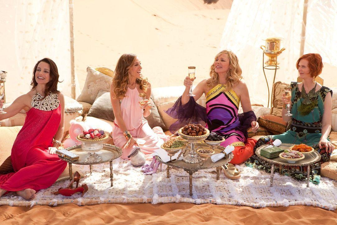 Auf einer Premierenfeier lernt Samantha (Kim Cattrall, 2.v.r.) einen arabischen Scheich kennen, der sich wünscht, dass sie die PR für sein neues Hot... - Bildquelle: Warner Brothers