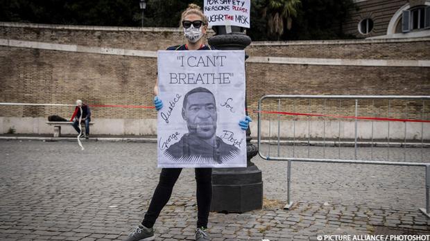 Eine Demonstrantin mit Plakat, auf dem George Floyd zu sehen ist, der von ein...