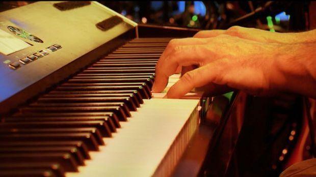 Hände, die auf dem Klavier spielen