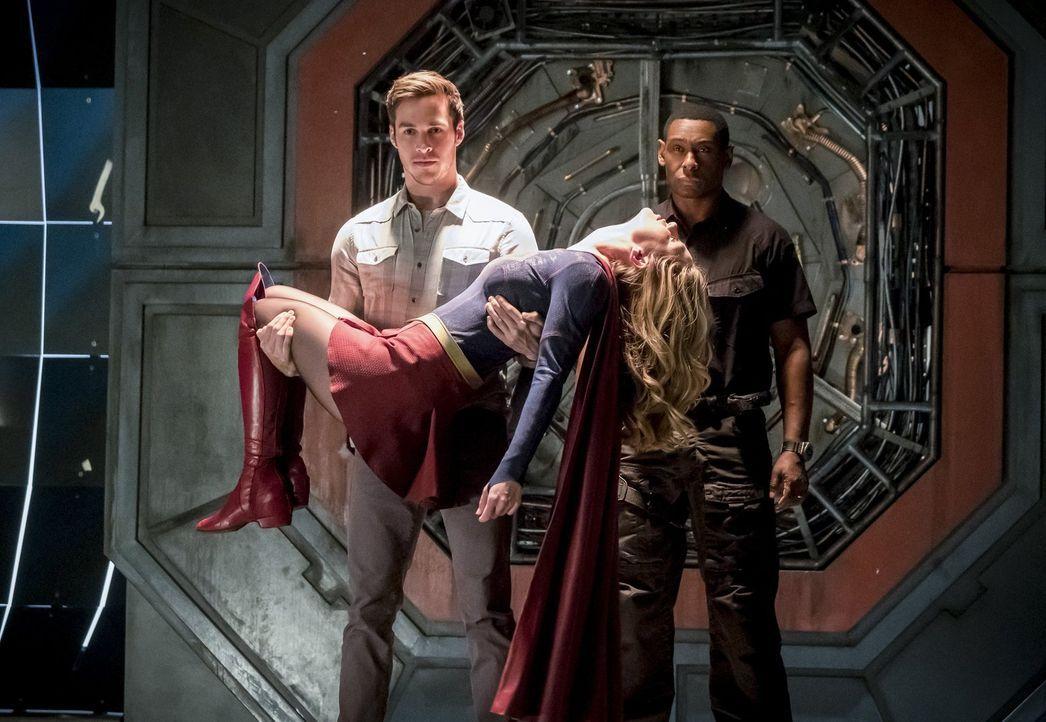 Mon-El (Chris Wood, l.) und J'onn (David Harewood, r.) tauchen mit einer vom Musik Meister ins Koma versetzten Supergirl (Melissa Benoist, vorne) au... - Bildquelle: 2016 Warner Bros.