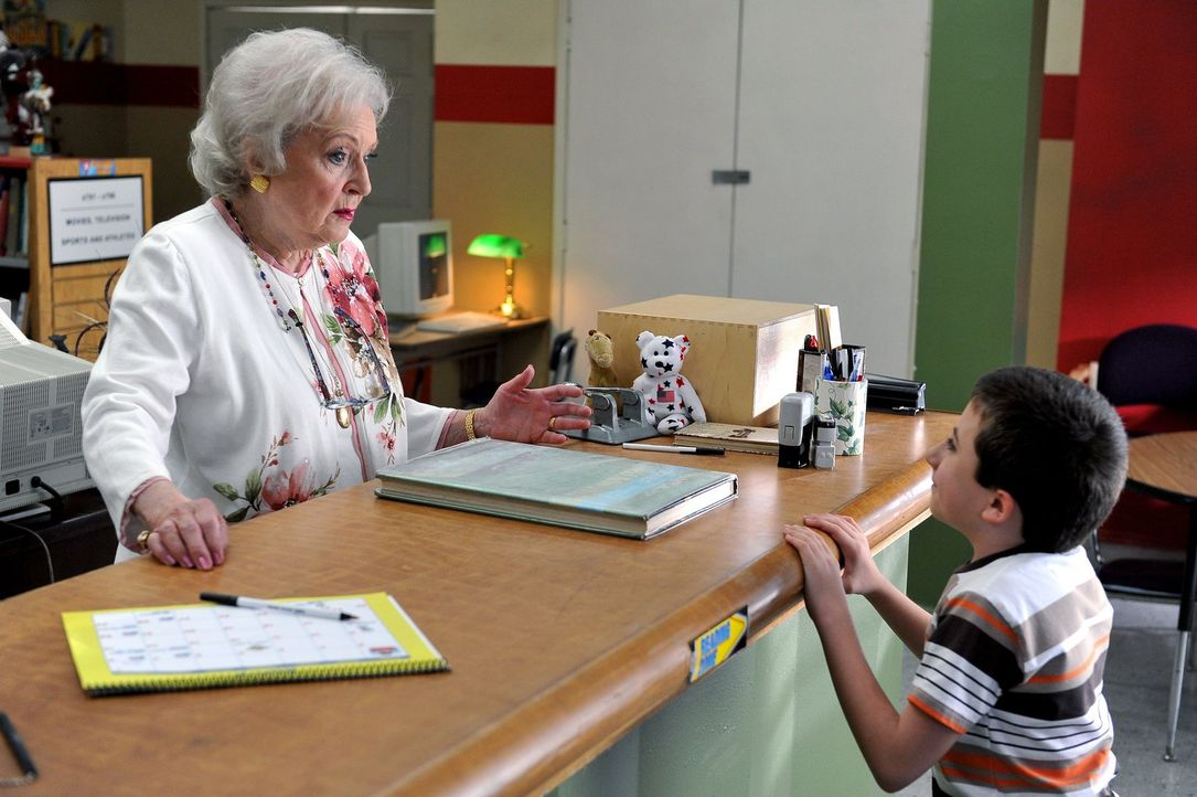 Als die Bibliothekarin Mrs. Nethercott (Betty White, l.) realisiert, dass Brick (Atticus Shaffer, r.) 31 Bibliotheksbücher offen hat, verlangt sie v... - Bildquelle: Warner Brothers