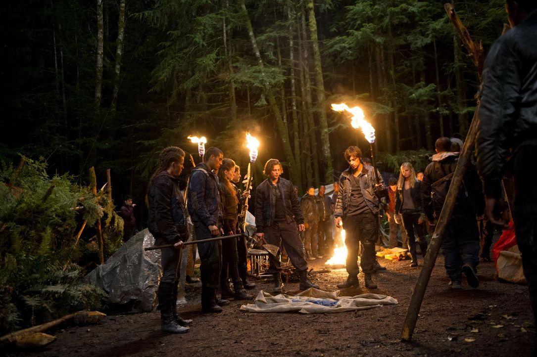 Als Jasper (Devon Bostick, 2.v.r.) und die anderen ins Camp zurückkehren, muss Clarke (Eliza Taylor, r.) erneut versuchen, Leben zu retten ... - Bildquelle: Warner Brothers