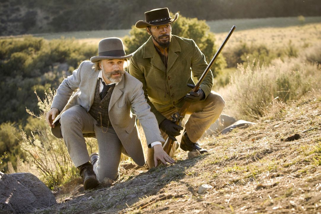 Um den Brittle-Brüdern auf die Spur zu kommen, befreit der belesene Kopfgeldjäger Dr. King Schultz (Christoph Waltz, l.) den Sklaven Django (Jamie F... - Bildquelle: 2012 Columbia Pictures Industries, Inc.  All Rights Reserved.