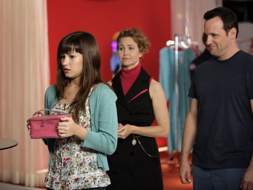 Aus der Prinzessin (Demi Lovato, l.) wird ein typisch amerikanisches Mädchen gestylt. Mason (Tom Verica, r.) und die Direktorin (Molly Hagan, M.) s... - Bildquelle: Disney